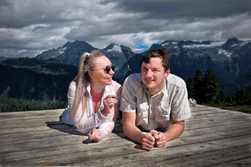 Lyckligt le folk som campar i berg Gift par på tältblocket som har roligt och avslappnande arkivbild