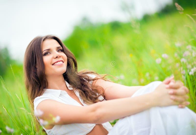 Lyckligt le härligt sammanträde för ung kvinna bland gräs och blommor arkivfoton