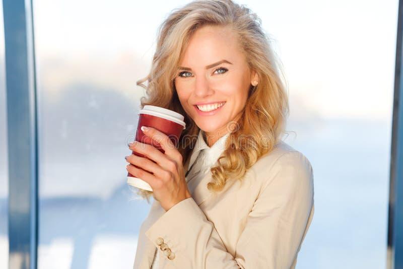 Lyckligt le hållande kaffe för affärskvinna nära fönster i regeringsställning royaltyfria foton