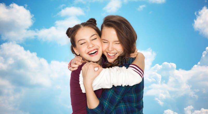 Lyckligt le nätt krama för tonårs- flickor royaltyfri bild