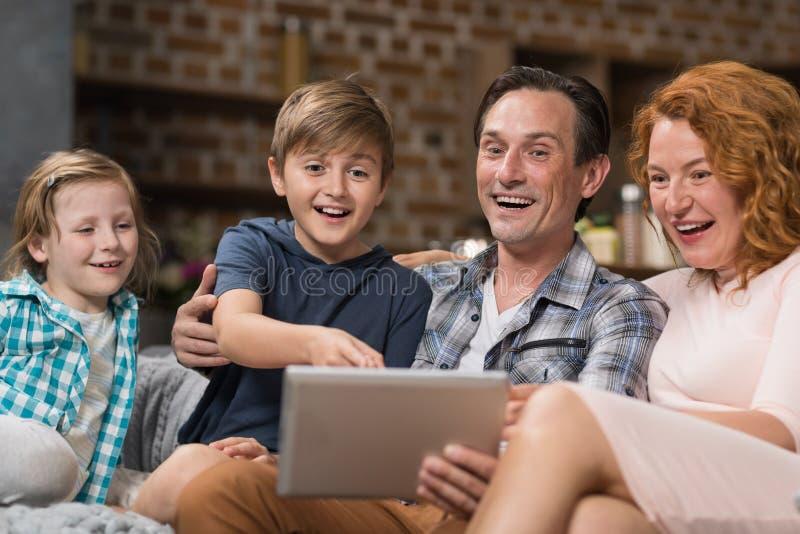Lyckligt le sammanträde för dator för familjbruksminnestavla på soffan i vardagsrum, föräldrar som spenderar Tid med sonen och do royaltyfria bilder