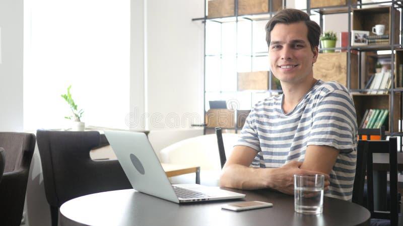 Lyckligt le som är tillfälligt, kopplar av mansammanträde i kontoret som ser kameran arkivbilder