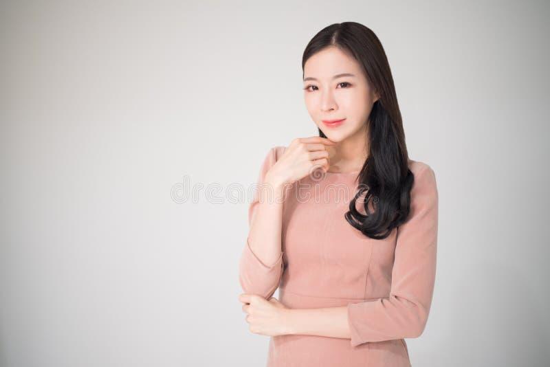 Lyckligt leende för härlig asiatisk kvinna med tillfällig kläder på vit b royaltyfri fotografi