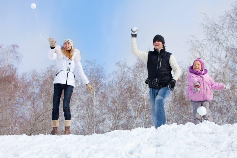 Lyckligt leka för familj kastar snöboll royaltyfri fotografi