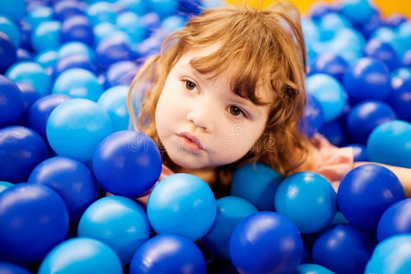Lyckligt liten flickabarn i färgglad blå plast- bollpöl arkivbild
