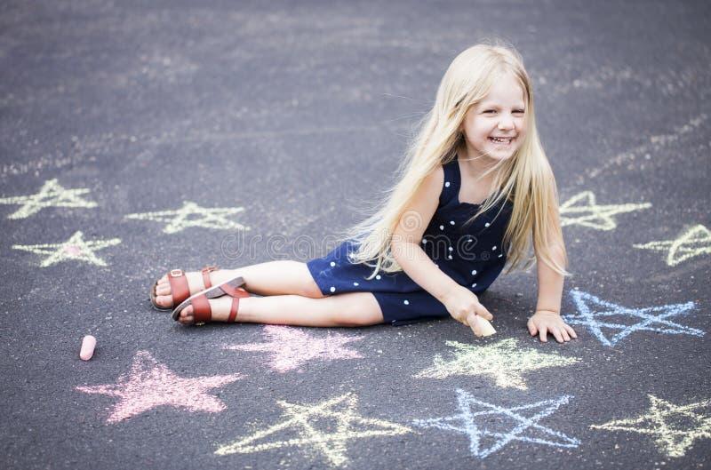 Lyckligt liten flickasammanträde på asfalt med målade stjärnor royaltyfri bild