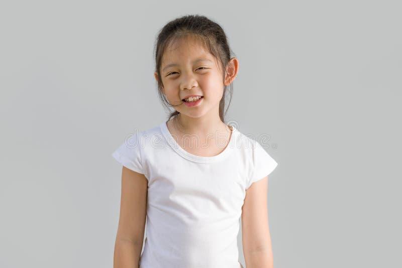 Lyckligt litet asiatiskt barn med den vita T-tröja som isoleras på vit bakgrund arkivbild