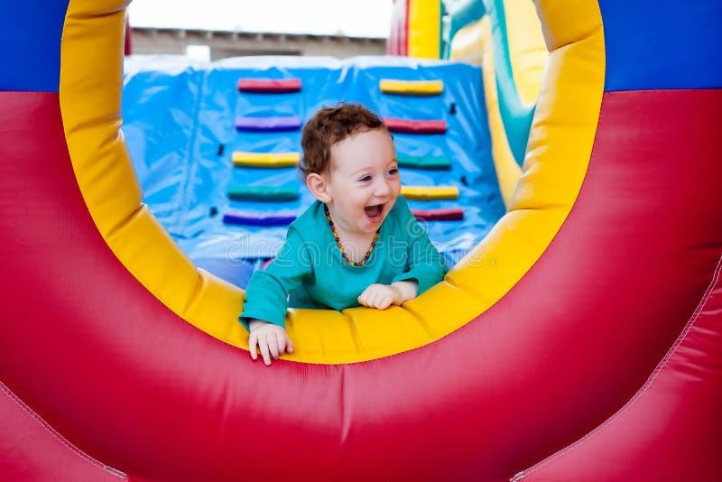 Lyckligt litet barn som kikar på trampolinen royaltyfri foto