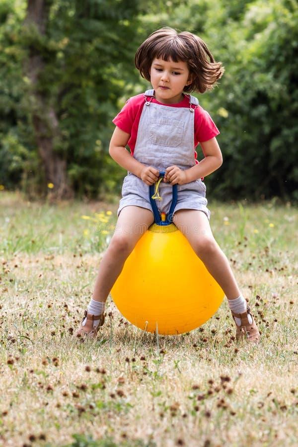 Lyckligt litet barn som studsar på en banhoppningboll för gyckel royaltyfri bild
