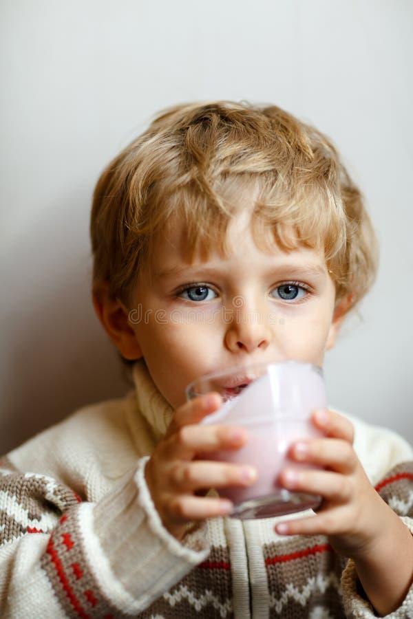 Lyckligt litet blont dricka för ungepojke mjölkar eller jordgubbemilkshake för frukost eller lunch Sunt äta för barn royaltyfri foto