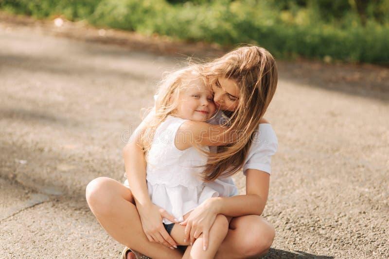 lyckligt ?lska f?r familj Fostra och hennes dotterbarnflicka som spelar och kramar gr?nd av stora tr?d Slapp fokus arkivfoton