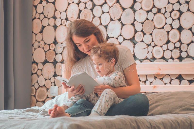 lyckligt ?lska f?r familj Nätt ung moder som läser en bok till hennes lilla son royaltyfri foto