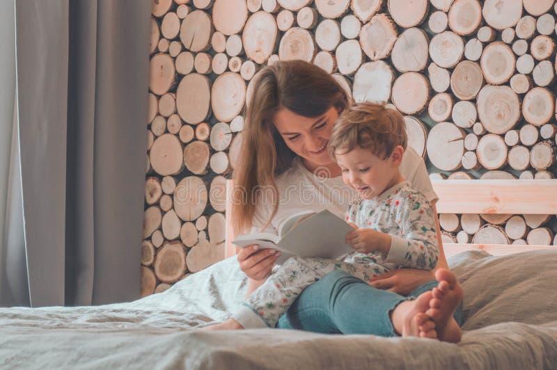 lyckligt ?lska f?r familj Nätt ung moder som läser en bok till hennes lilla son royaltyfria bilder