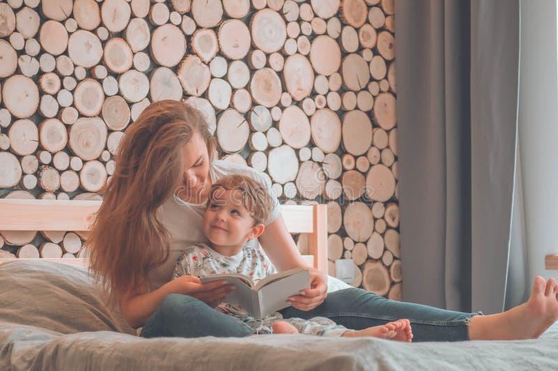 lyckligt ?lska f?r familj Nätt ung moder som läser en bok till hennes lilla son arkivfoto