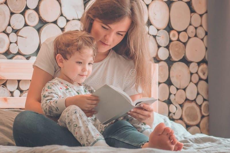 lyckligt ?lska f?r familj Nätt ung moder som läser en bok till hennes lilla son royaltyfri bild