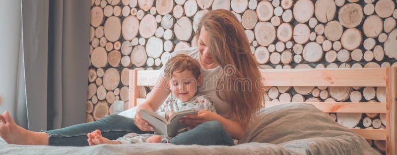 lyckligt ?lska f?r familj Nätt ung moder som läser en bok till hennes lilla son royaltyfria foton