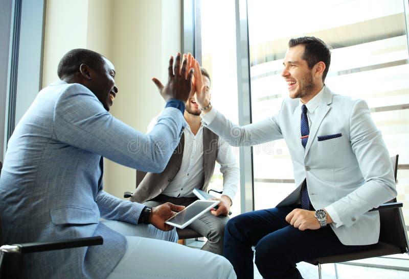 Lyckligt lyckat blandras- affärslag som ger en höjdpunktpickolaflöjtgest, som de skrattar och hurrar deras framgång arkivbild