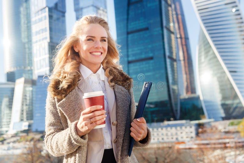 Lyckligt lyckat kaffe och mapp för affärskvinna hållande med dokument royaltyfri fotografi