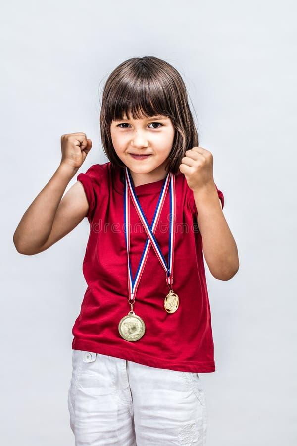 Lyckligt lyckat pojkaktigt barn med medaljer som är villiga att segra utmärkelsen fotografering för bildbyråer
