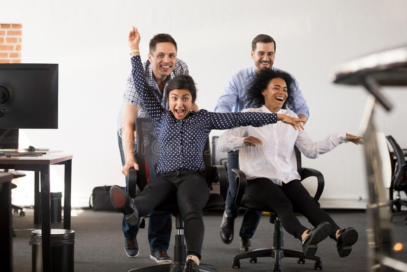 Lyckligt mång--person som tillhör en etnisk minoritet kontorsfolk som har gyckel som rider på stolar arkivbilder