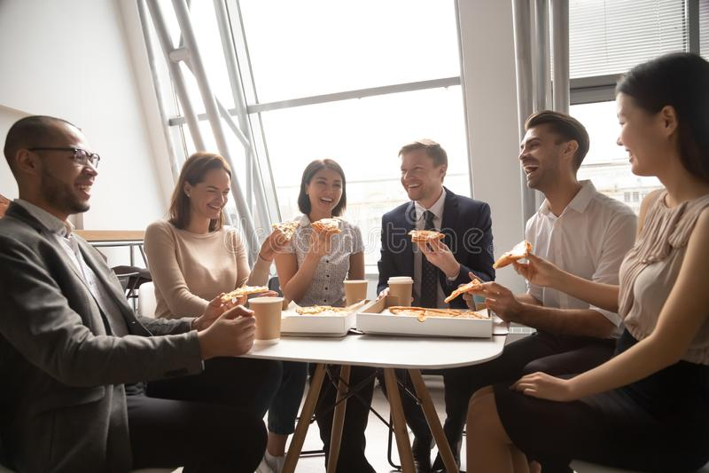 Lyckligt mångkulturellt lag för personalarbetaraffär som har gyckel som äter pizza arkivfoto