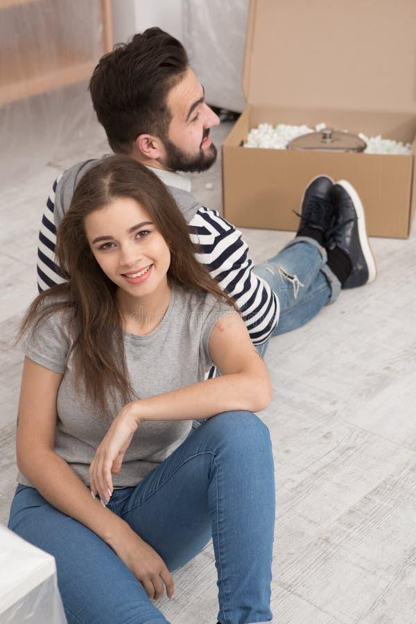 Lyckligt man- och kvinnasammanträde på golvet tröttade att förbereda sig att förflytta till den nya lägenheten arkivbilder