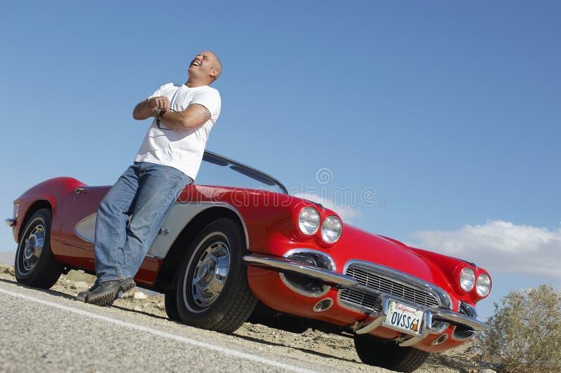 Lyckligt mananseende bredvid den klassiska bilen på vägen arkivfoto