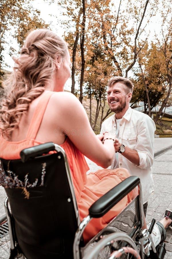 Lyckligt mananseende på ett knä och fråga hans flickvän att att gifta sig honom arkivbilder