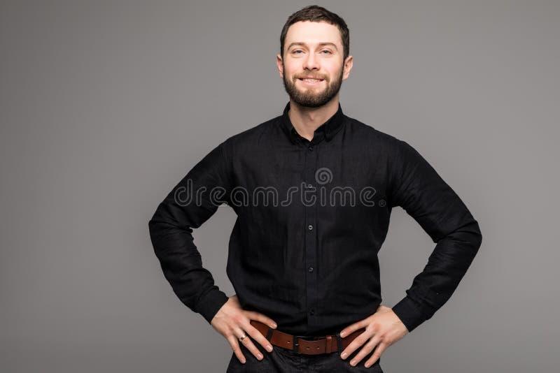 lyckligt manbarn Stående av den stiliga unga mannen i tillfällig skjorta som ler, medan stå mot grå bakgrund royaltyfri bild