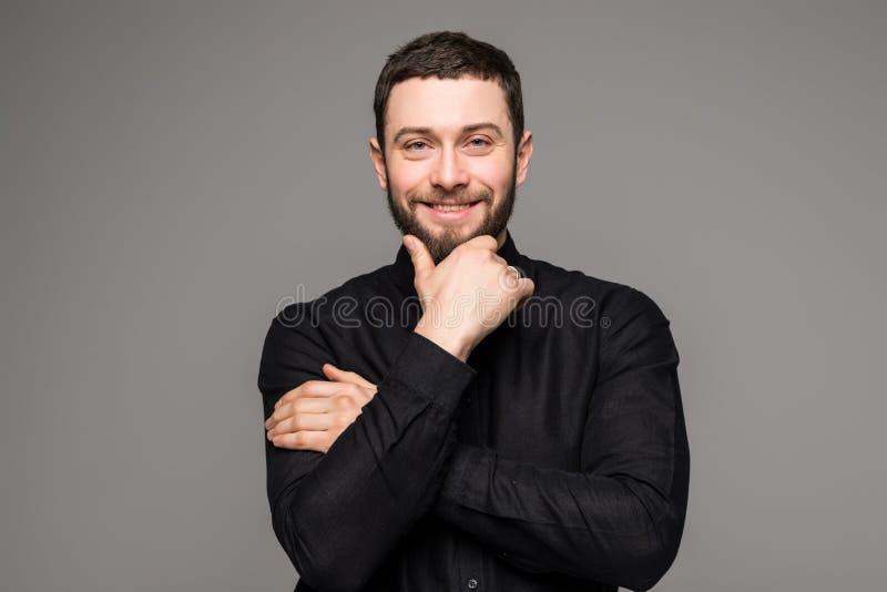 lyckligt manbarn Stående av den stiliga unga mannen i tillfällig skjorta som ler, medan stå mot grå bakgrund royaltyfria bilder