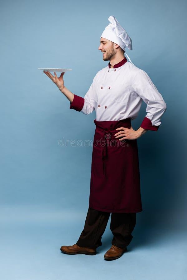 Lyckligt manligt kockkockanseende med plattan som isoleras på ljust - blå bakgrund fotografering för bildbyråer