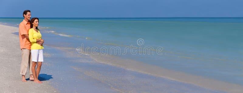 Lyckligt, mannen och kvinnan koppla ihop på en tom strandpanorama royaltyfri fotografi
