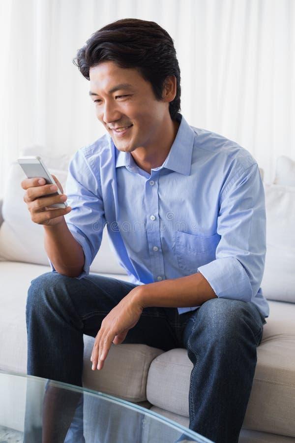 Lyckligt mansammanträde på soffan som smsar på telefonen arkivfoto