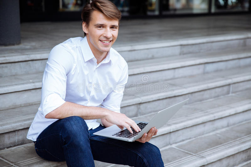 Lyckligt mansammanträde utomhus och genom att använda bärbara datorn arkivfoto