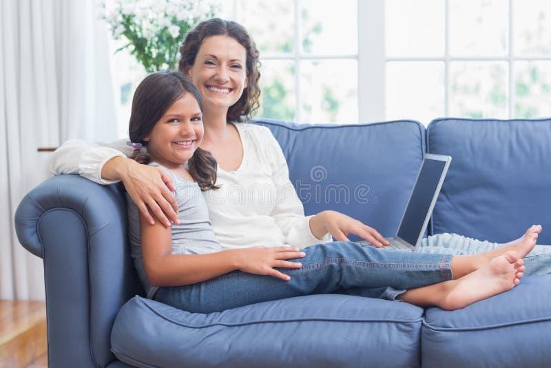 Lyckligt moder- och dottersammanträde på soffan och användabärbara datorn arkivfoto