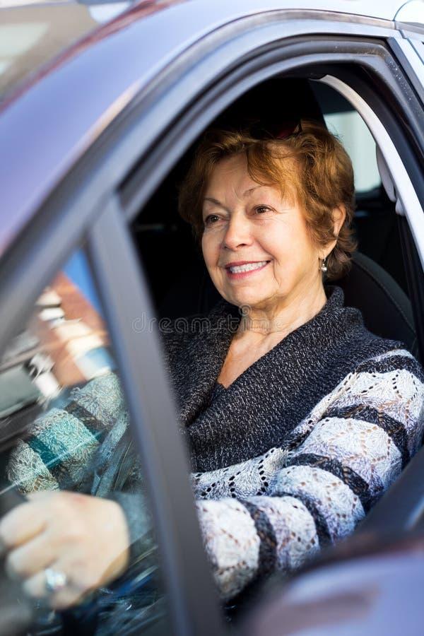 Lyckligt moget kvinnasammanträde i ny bil royaltyfri fotografi