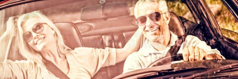 Lyckligt mogna par i röd cabriolet royaltyfria foton