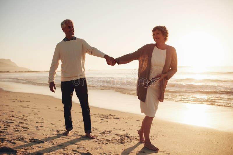 Lyckligt mogna par som promenerar stranden royaltyfri fotografi