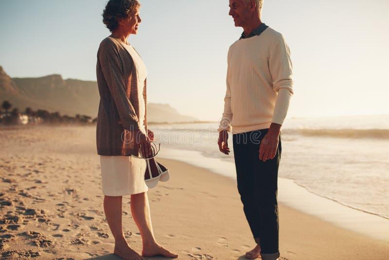 Lyckligt mogna par som tillsammans står på stranden arkivbild