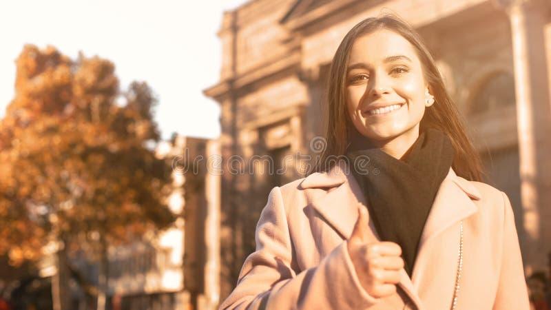 Lyckligt motiverat kvinnligt le n?ra universitetbyggnad som visar tummar-upp fotografering för bildbyråer