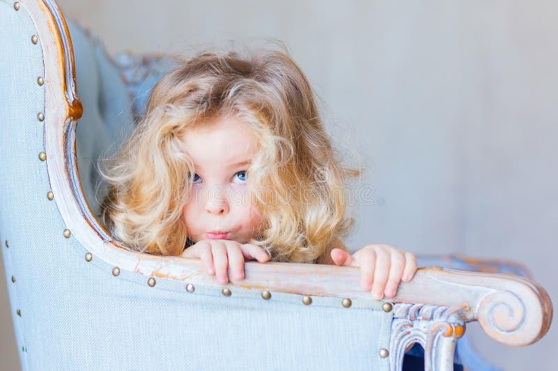 Lyckligt nätt litet barnflickasammanträde som ser kuriositeter royaltyfri fotografi