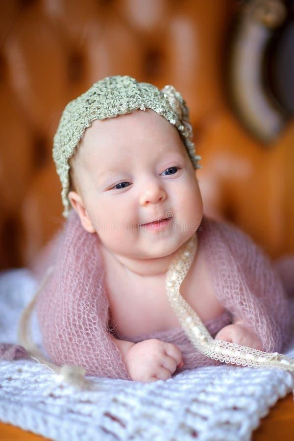 Lyckligt nyfött behandla som ett barn lögner på en stol i en härlig stucken hatt, med intresse ser omkring, joyfully leenden royaltyfri foto