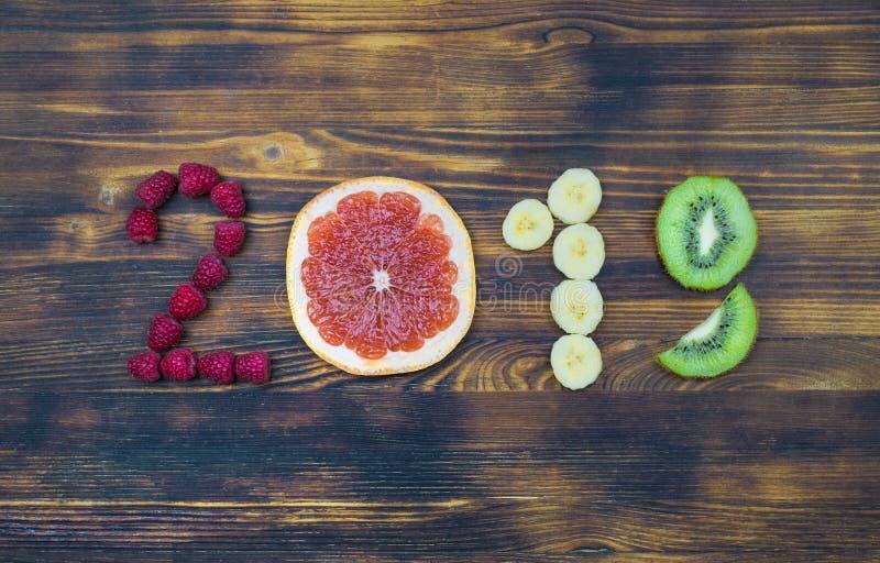 Lyckligt nytt år 2019 av frukt och bär på träbakgrund royaltyfri foto