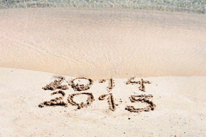 Lyckligt nytt år 2015 byter ut begreppet 2014 på havsstranden arkivbild