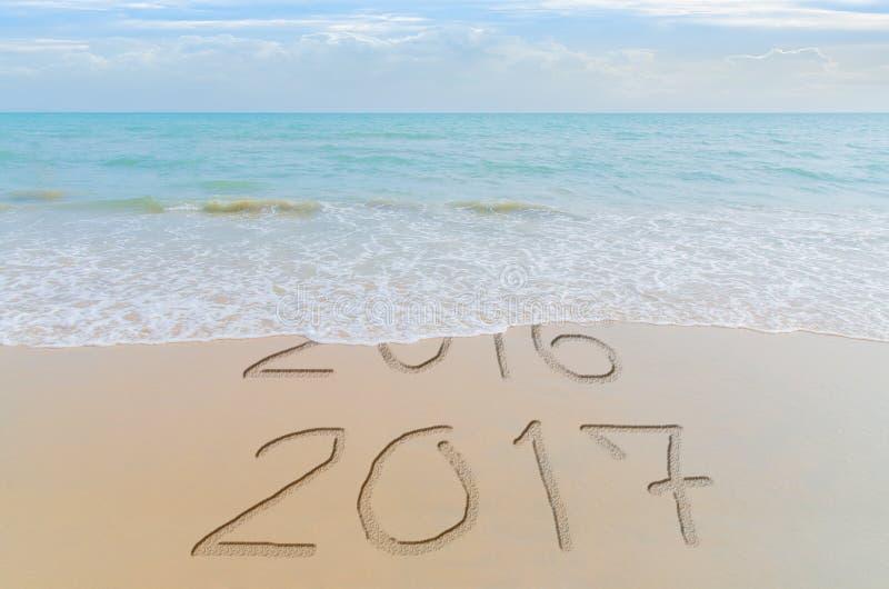 Lyckligt nytt år 2017 byter ut begreppet 2016 på sommarhavsstranden Det nya året 2017 är det kommande begreppet royaltyfri fotografi