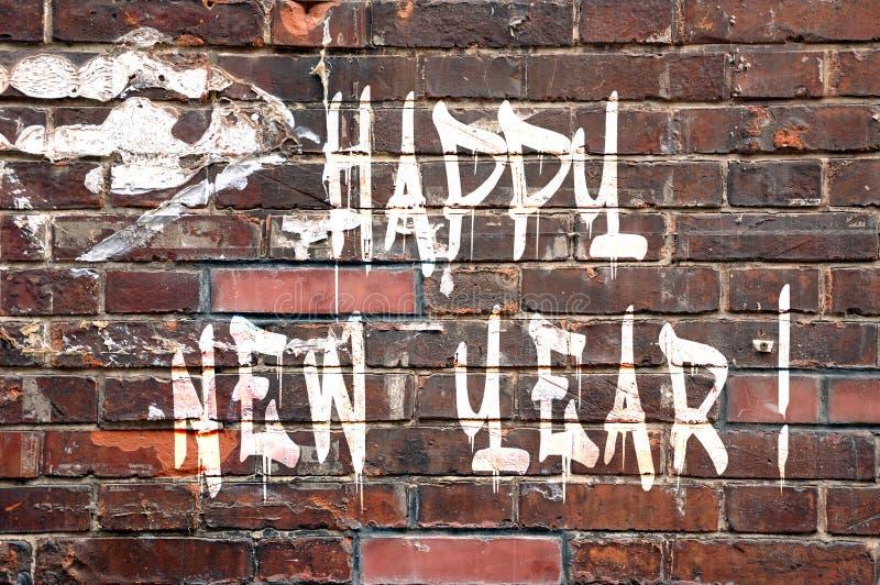 Lyckligt nytt år på en tegelstenvägg royaltyfri bild