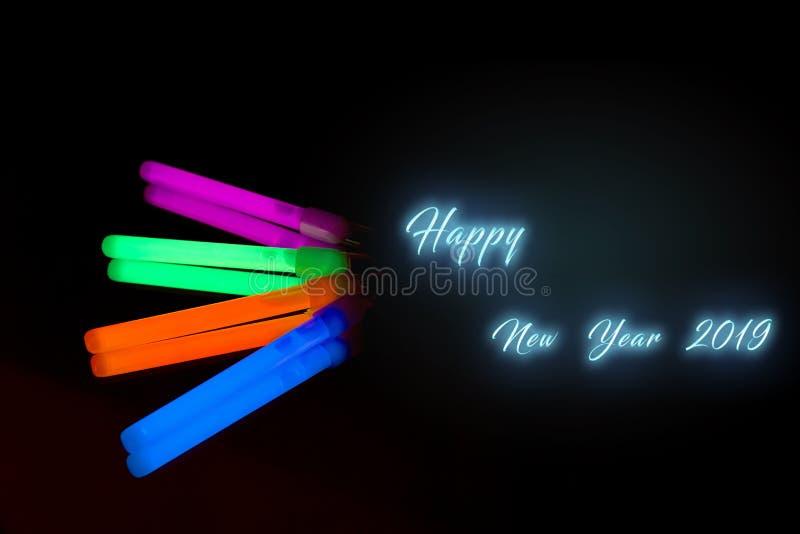Lyckligt nytt år 2019 Pinne för glöd för färgrikt lysrörneon stor på bakgrund för svart för spegelreflexion arkivbild