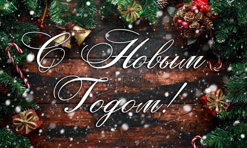 Lyckligt nytt år som visas på en lantlig trätabell med garnering, gåvor, snö, trädfilial i ryss arkivbilder