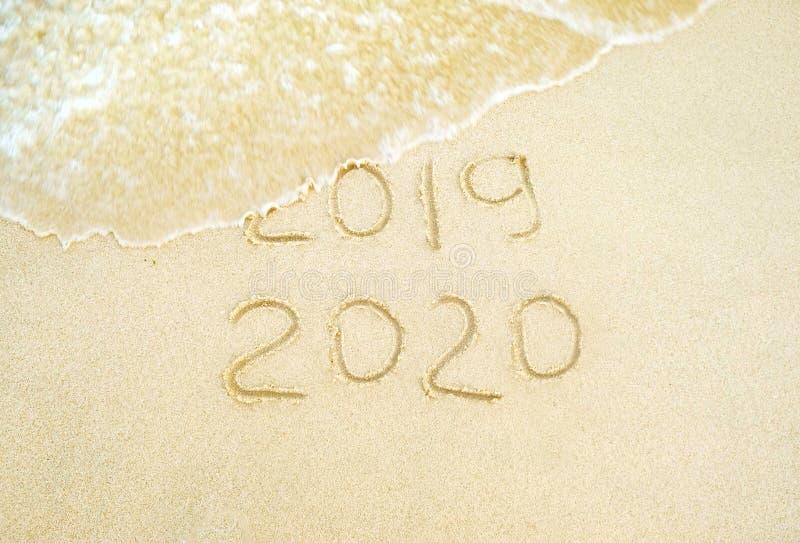 lyckligt nytt ?r 2020 och 2019 som ?r skriftliga p? sanden var 2019 f?r tv?ttad bort av v?gen royaltyfri bild