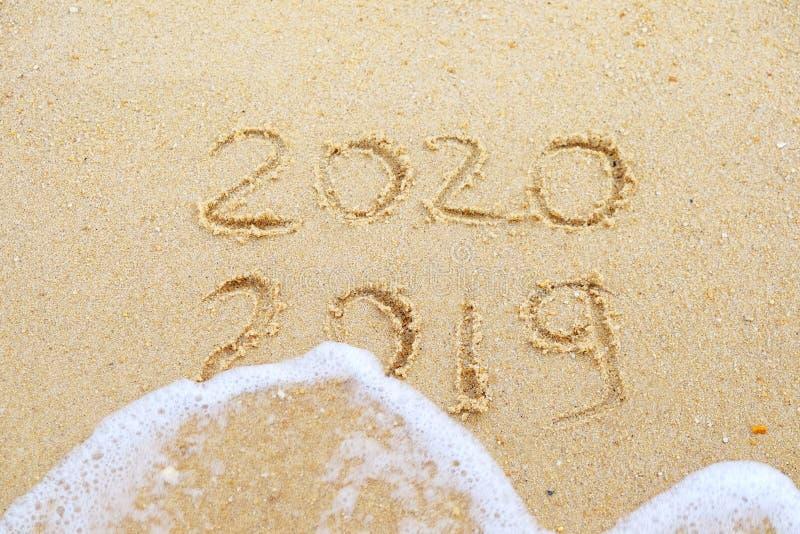 lyckligt nytt ?r 2020 och 2019 som ?r skriftliga p? sanden var 2019 f?r tv?ttad bort av v?gen royaltyfria bilder